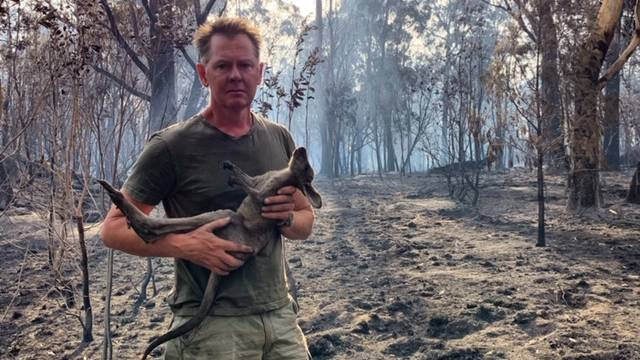 Conservationist Steve Haslam with an Eastern Grey kangaroo joey caught in the inferno which devastated his Talmoi Road property. Mr Haslam said we need new fire management strategies to cope with a new climate.